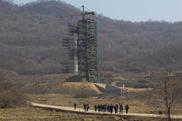 FILE - In this April 8, 2012 file photo, a group of journalists walk down a road in front of North Korea's Unha-3 rocket at Sohae Satellite Station in Tongchang-ri, North Korea. April 8, 2012. North Korea said Saturday, Dec. 1, 2012 it will launch a long-range rocket between Dec. 10 and Dec. 22. The launch will heighten already strained tensions with South Korean ahead of its presidential election on Dec. 19. (AP Photo/David Guttenfelder, File)