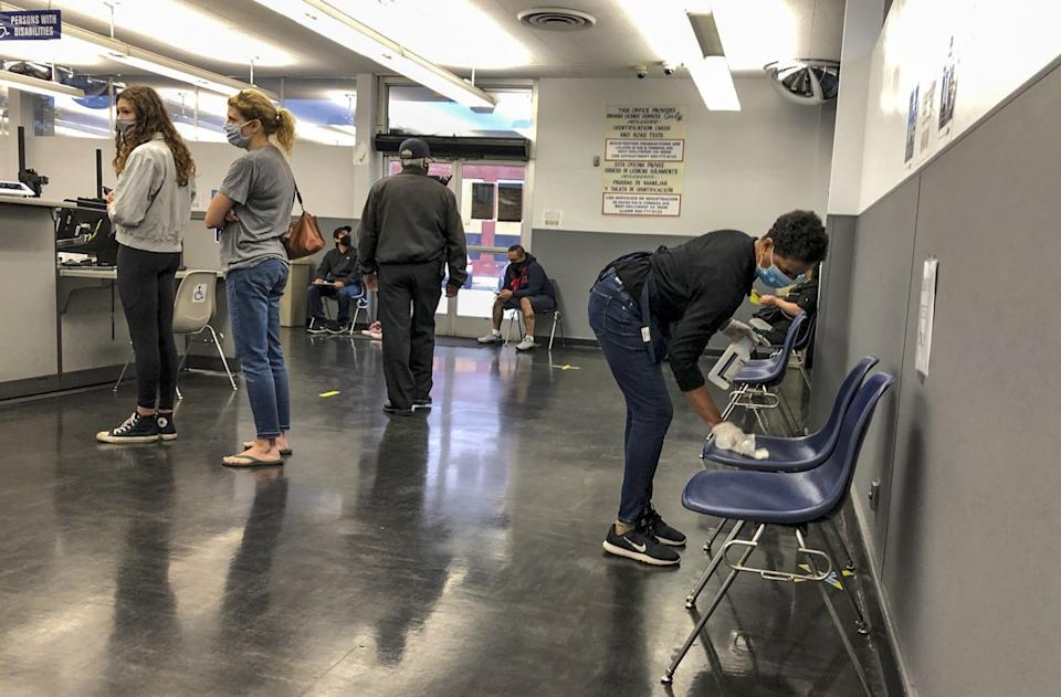 "Masked customers wait in line at the Hollywood DMV office, left, with a security guard, center, and a DMV employee spraying and wiping down chairs. <span class=""copyright"">(Adam Tschorn / Los Angeles Times)</span>"