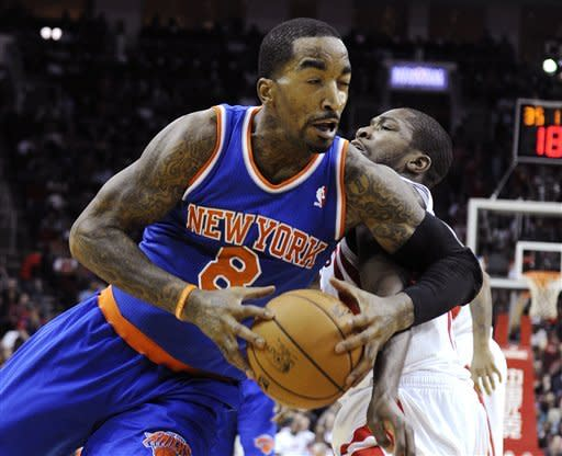 New York Knicks' J.R. Smith (8) is fouled by Houston Rockets' Toney Douglas, right, in the first half of an NBA basketball game, Friday, Nov. 23, 2012, in Houston. (AP Photo/Pat Sullivan)