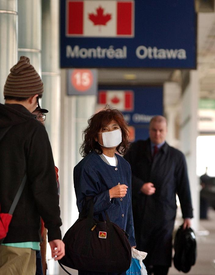 A passenger wears a face mask to protect against the SARS virus, while waiting for a shuttle outside Pearson International Airport in Toronto, Canada, Wednesday, April 23, 2003. (AP Photo/CP/Globe and Mail, J.P. Moczulski) ORG XMIT: CPT120