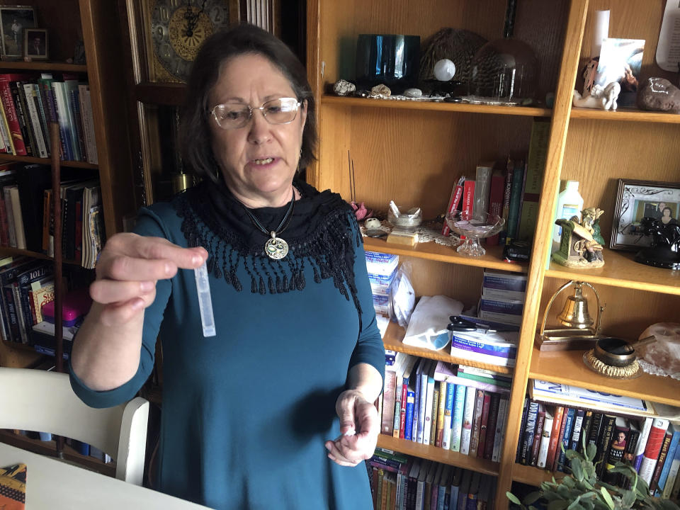 Barbara Trout, who has an asthma disorder, holds a vial of inhalation solution of Ipratropium Bromide and Albuterol Sulfate, prescribed medication at her home in Keizer, Ore., Wednesday, Oct. 14, 2020. (AP Photo/Andrew Selsky)