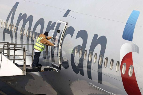 PHOTO: A worker closes the door on an American Airlines plane at a gate at John F. Kennedy International Airport in New York, March 26, 2021. (Angus Mordant/Bloomberg via Getty Images, FILE)