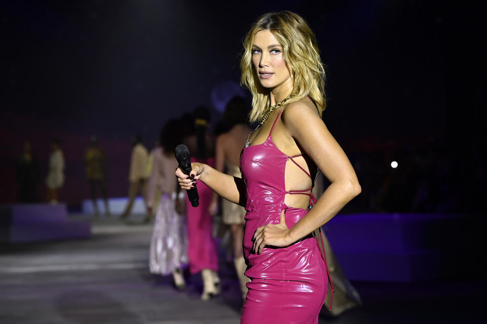 Singer Delta Goodrem wears a magenta pink latex dress while performing as models walk the runway during the Manning Cartell show during Afterpay Australian Fashion Week 2021 Resort '22 Collections at Carriageworks on June 03, 2021 in Sydney, Australia