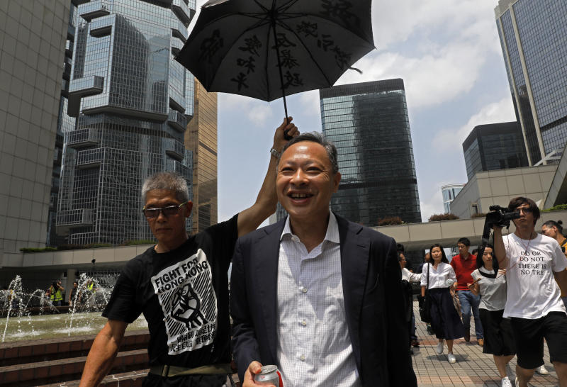 Occupy Central leader Benny Tai, center, is accompanied by a supporter who raises an umbrella as he leaves High court in Hong Kong Thursday, Aug. 15, 2019. Tai, a top opposition leader imprisoned on public disorder charges was released on bail Thursday as Hong Kong's government attempts to quell a protest movement that has paralyzed parts of the territory, including its international airport, and led to hundreds of arrests. (AP Photo/Vincent Yu)