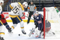 Columbus Blue Jackets' Elvis Merzlikins, right, makes a save against Nashville Predators' Alexandre Carrier during the third period of an NHL hockey game Wednesday, May 5, 2021, in Columbus, Ohio. The Blue Jackets won 4-2. (AP Photo/Jay LaPrete)