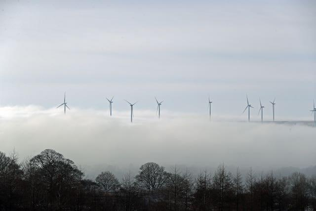 Wind turbines peak out of the top of low-lying clouds over Lancashire