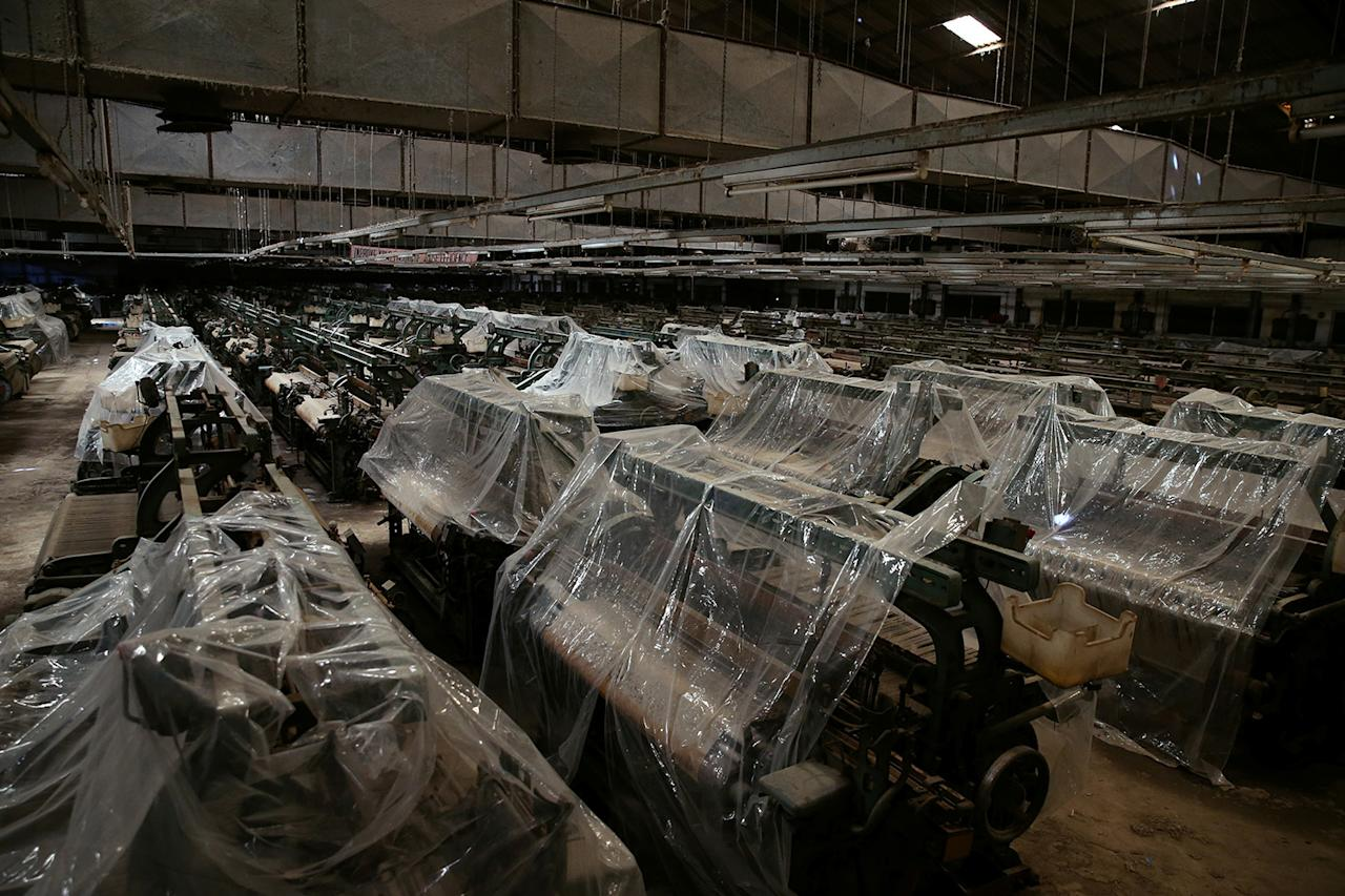 <p>Textile-weaving machines are covered at a closed-down textile factory in Kaduna, Nigeria, on Nov. 3, 2016. (Photo: Afolabi Sotunde/Reuters) </p>