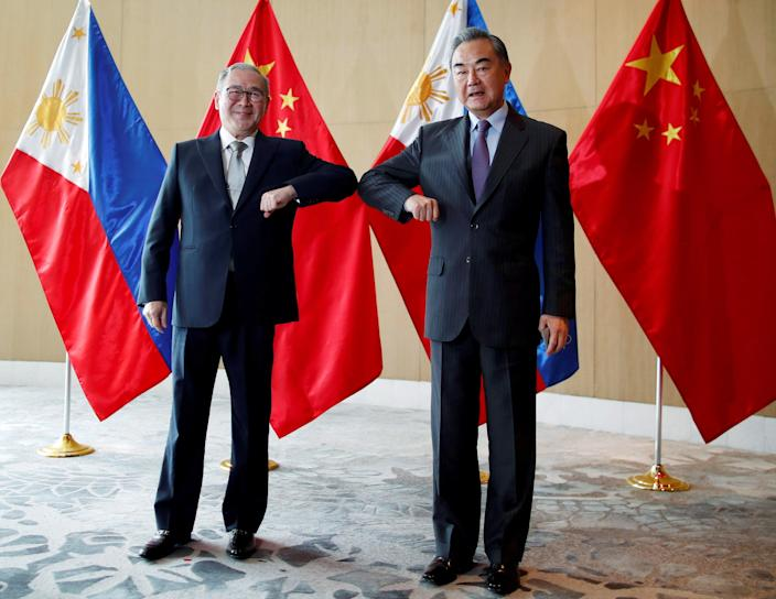 <p>File image: China's Foreign Minister Wang Yi and Philippine's Foreign Affairs Secretary Teodoro Locsin Jr bump their elbows during a meeting in Manila, Philippines on 16 January, 2021</p> (Reuters)