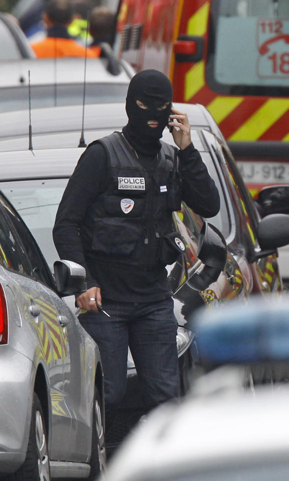 A police officer stands next to the building in Toulouse, France, Wednesday March 21, 2012 where a suspect in the shooting at the Ozar Hatorah Jewish school has been spotted. A father and his two sons were among four people who died Monday when a gunman opened fire in front of a Jewish school in the city in southwest France. (AP Photo/Remy de la Mauviniere)