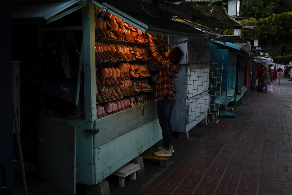 A merchant closes her shop for the day on Olvera Street in downtown Los Angeles, Tuesday, Dec. 15, 2020. Olvera Street, known as the birthplace of Los Angeles, has been particularly hard hit by the coronavirus pandemic, with shops and restaurants closed and others barely hanging on. Only a handful of businesses remain open on weekdays as tourism has cratered and downtown offices are closed and festive events held throughout the year have been canceled. (AP Photo/Jae C. Hong)