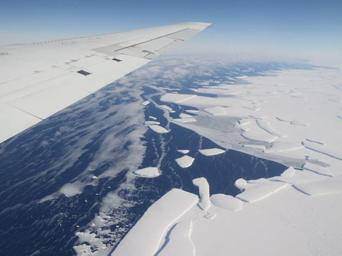 An aerial view of an ice shelf in western Antarctica shedding icebergs.