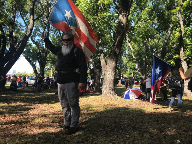 "German Alejandro Ortiz, a 43-year-old businessman holds a Puerto Rico flag as he poses for a photo during a protest to demand the resignation of Governor Ricardo Rossello, in San Juan, Puerto Rico, Monday, July 22, 2019. Ortiz explained why he decided to join the protest: ""Our people are suffering...We need leaders who will truly take care of our people, not of their friends."" (AP Photo/Danica Coto)"