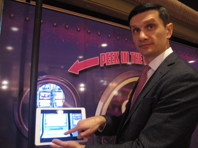 Kresimir Spajic, senior vice president of online gaming at Hard Rock International, uses a hand-held tablet computer to activate and play a slot machine located in a room behind him at the Hard Rock casino in Atlantic City N.J., Monday, Feb. 10, 2020. The technology lets people use the internet to gamble on real-life slot machines that are inside the casino. (AP Photo/Wayne Parry)