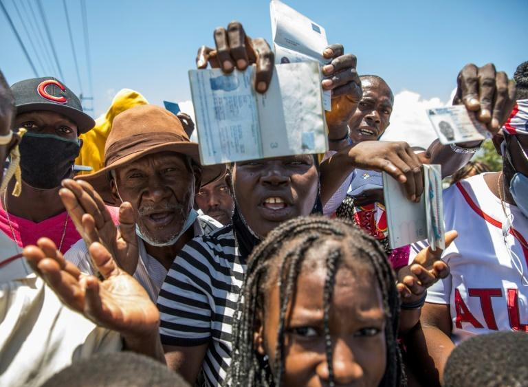 Haitian citizens hold up their passports as they gather in front of the US Embassy outside Port-au-Prince