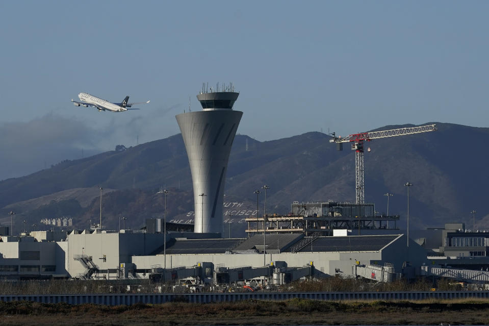 A plane takes off behind the air traffic control tower at San Francisco International Airport during the coronavirus outbreak in San Francisco, Tuesday, Nov. 24, 2020. (AP Photo/Jeff Chiu)