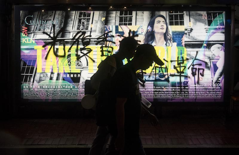 HONG KONG, CHINA - AUGUST 18: Demonstrators pass by a vandalized street advertisement during a protest organized by the Civil Human Rights Front, in Hong Kong, China on August 18, 2019. Large-scale protests in Hong Kong began last June against a bill to legalize the extradition of suspects to mainland China, Macao and Taiwan. (Photo by Miguel Candela/Anadolu Agency via Getty Images)