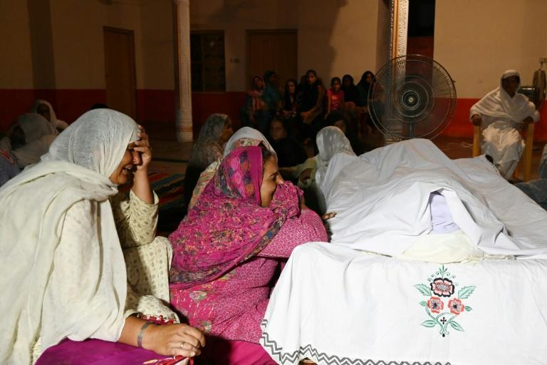 Pakistani mourners gather around the body of a victim, one of at least 19 killed in the earthquake that hit northeastern Pakistan