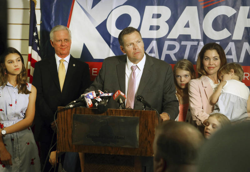 Secretary of State Kris Kobach, surrounded by his family and running mate Wink Hartman, talked to the media during a news conference at the Topeka Capitol Plaza hotel in Topeka, Kan., Wednesday, Aug. 8, 2018. (Thad Allton /The Topeka Capital-Journal via AP)