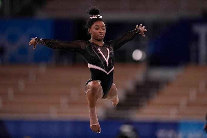 Simone Biles, of the United State, trains on the floor exercise during an artistic gymnastics practice session at the 2020 Summer Olympics, Thursday, July 22, 2021, in Tokyo, Japan. (AP Photo/Gregory Bull)