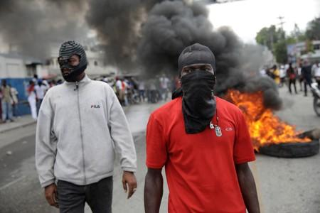 Masked protesters stand next to a burning barricade during a demonstration to demand the resignation of Haitian president Jovenel Moise, in the streets of Port-au-Prince