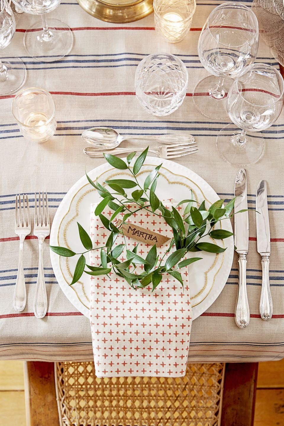 <p>A bit of greenery is all your neutral linens need. After making name cards with cut cardboard, secure the tags to a circle of leaves welcoming each guest.<br></p>