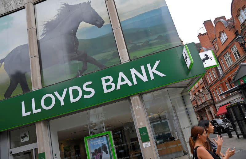 FILE PHOTO: A woman looks at her phone as she walks past a branch of Lloyds bank in London, Britain