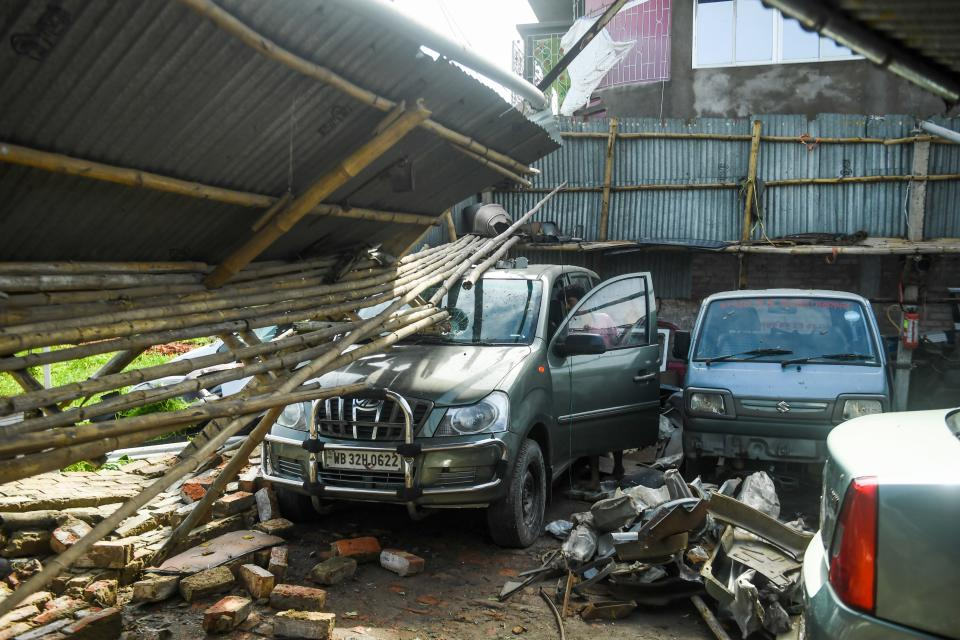 A man checks cars in a garage damaged by cyclone Amphan in Satkhira on May 21, 2020. (Photo by MUNIR UZ ZAMAN/AFP via Getty Images)