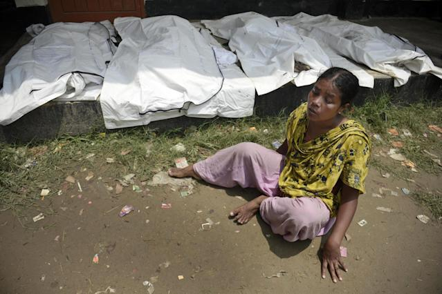 A woman cries as she looks for her missing sister next to covered dead bodies laid out, near the site of a garment factory building that collapsed in Savar near Dhaka, Bangladesh, Wednesday May 8, 2013. Dozens of bodies recovered Wednesday from the building were so decomposed they were being sent to a lab for DNA identification, police said, as the death toll from Bangladesh's worst industrial disaster topped 800. (AP Photo/Ismail Ferdous)