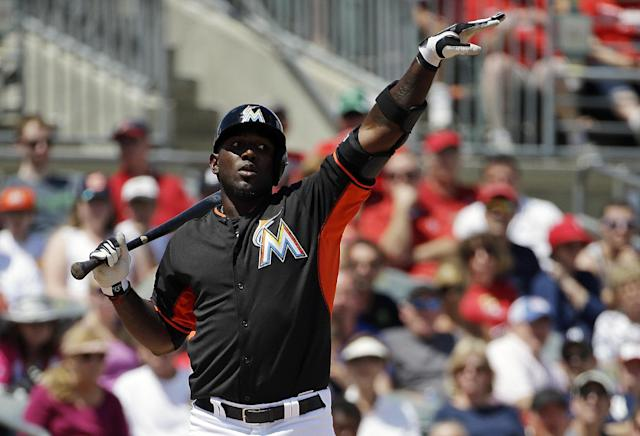Miami Marlins' Marcell Ozuna gestures to teammate Jarrod Saltalamacchia to run on a wild pitch in the second inning of an exhibition spring training baseball game against the St. Louis Cardinals, Tuesday, March 25, 2014, in Jupiter, Fla. (AP Photo/David Goldman)