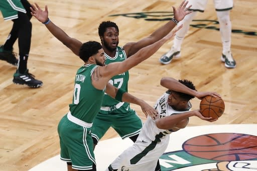 Boston Celtics' Jayson Tatum (0) and Semi Ojeleye (37) defend against Milwaukee Bucks' Giannis Antetokounmpo (34) during the first half of an NBA basketball game Wednesday, Dec. 23, 2020, in Boston. (AP Photo/Michael Dwyer)