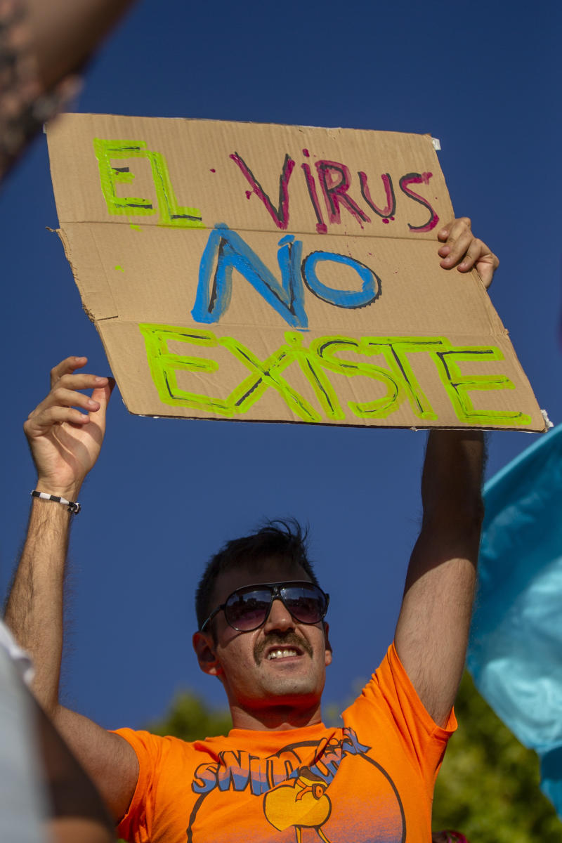 "A demonstrator attends a protest against nationwide restrictions against COVID-19 in Madrid, Spain, Sunday, Aug. 16, 2020. Banner reads in Spanish ""The Virus doesn't exist"". (AP Photo/Andrea Comas)"