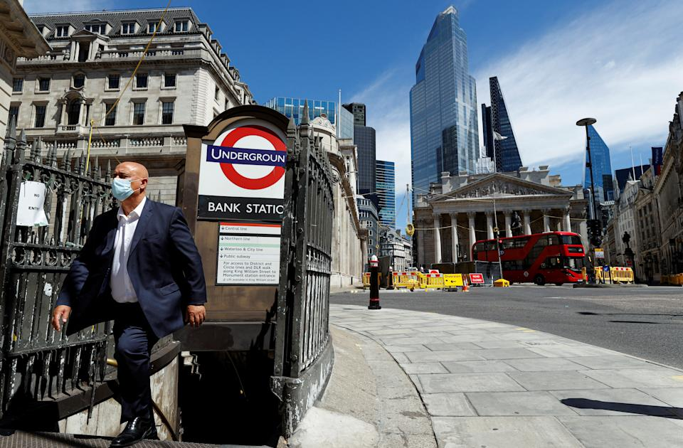 A man wearing a face mask and suit exits Bank underground station, in front of the Bank of England and Royal Exchange Building, amid the coronavirus disease (COVID-19) outbreak, in London, Britain, July 30, 2020.  REUTERS/John Sibley