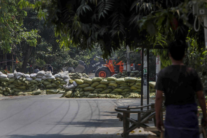 A man watches as soldiers use a bulldozer to remove sandbag barricades put in place by anti-coup protesters to protect them from security forces in Mandalay, Myanmar, Thursday, March 18, 2021. (AP Photo)