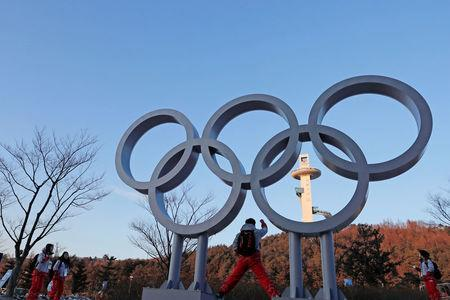 Volunteers pose next to the Olympic rings at the Pyeongchang Winter Olympic Games in Pyeongchang, South Korea February 7, 2018. REUTERS/Jorge Silva