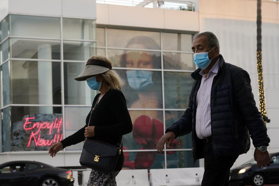 FILE - In this Dec. 9, 2020, file photo, masked pedestrians walk past of a COVID 19-themed mural depicting Leonardo da Vinci's Mona Lisa in Beverly Hills, Calif. The first COVID-19 vaccinations are underway at U.S. nursing homes, where the virus has killed upwards of 110,000 people, even as the nation struggles to contain a surge so alarming that California is dispensing thousands of body bags and lining up refrigerated morgue trailers. (AP Photo/Marcio Jose Sanchez, File)