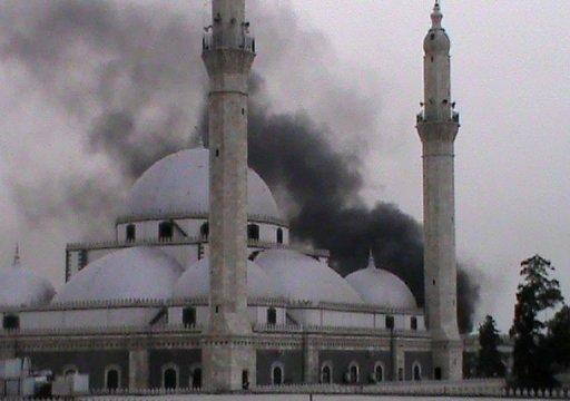 Smoke rises from a mosque following shelling by government forces on the Khalidiyah neighbourhood of Homs