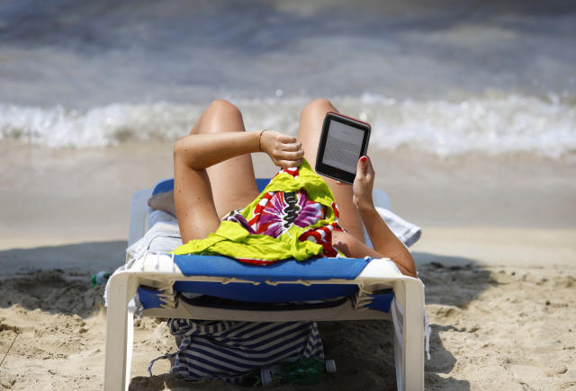 Mujer lee en la playa en un eBook. Foto: Clara Margais / Getty Images