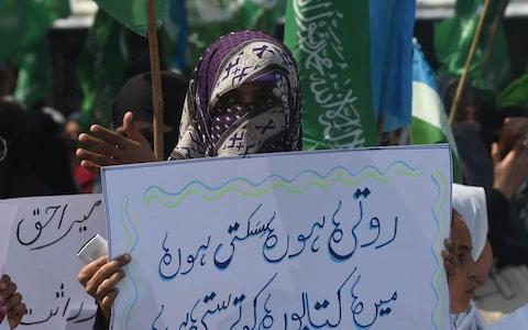 A woman holds up a placard in Lahore, Pakistan - Credit: AFP/Getty Images