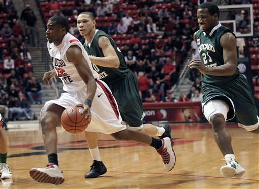 San Diego State guard Chase Tapley, left, dribbles past Chicago State's Matt Samuels, right, and Lee Fisher, center, in the first half of an NCAA college basketball game Tuesday, Jan. 10, 2012, in San Diego. (AP Photo/Gregory Bull)