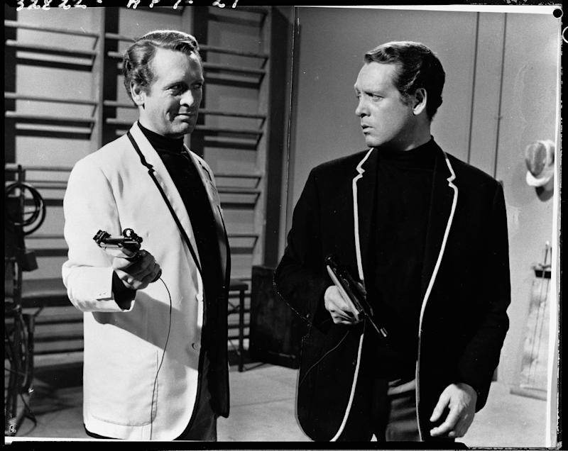 American-born Irish actor Patrick McGoohan in character as both Number Six (right) and his doppelganger Charles Curtis, Number 12, as they hold sporting pistols and look at each other in a gymnasium during the episode 'Schizoid Man' of the cryptic adventure series 'The Prisoner,' United Kingdom, 1968. (Photo by CBS Photo Archive/Getty Images)