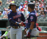 Minnesota Twins' Jorge Polanco (11) shakes hands with Luis Arraez (2) after scoring on a double in the first inning of a baseball game against the Texas Rangers, Sunday, Aug. 18, 2019, in Arlington, Texas. (AP Photo/Richard W. Rodriguez)