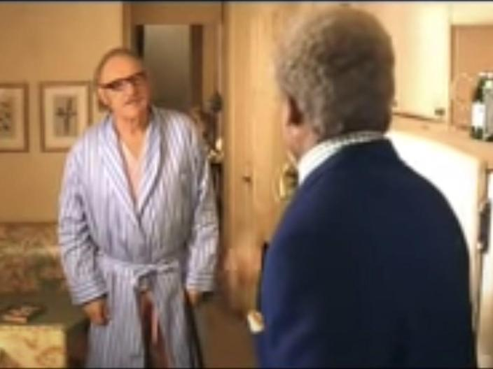 Royal Tenenbaum (Gene Hackman) stands in a bathrobe in the family's kitchen while arguing with Henry (Danny Glover), who has his back to the viewer.