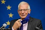 Top EU diplomat Josep Borrell removes his face mask prior to speaking during a press conference following a meeting at the United Nations of EU foreign ministers that touched on a US-French row (AFP/Angela Weiss)