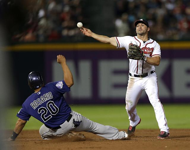 Atlanta Braves second baseman Dan Uggla forces out Colorado Rockies' Wilin Rosario (20) at second base as he turns a double play on a Nolan Arenado ground ball in the eight inning of a baseball game in Atlanta, Monday, July 29, 2013. (AP Photo/John Bazemore)