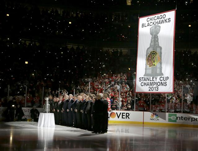 The Chicago Blackhawks stand with the Stanley Cup and the championship banner during ceremonies before an NHL hockey game between the Blackhawks and the Washington Capitals Tuesday, Oct. 1, 2013, in Chicago. (AP Photo/Nam Y. Huh)