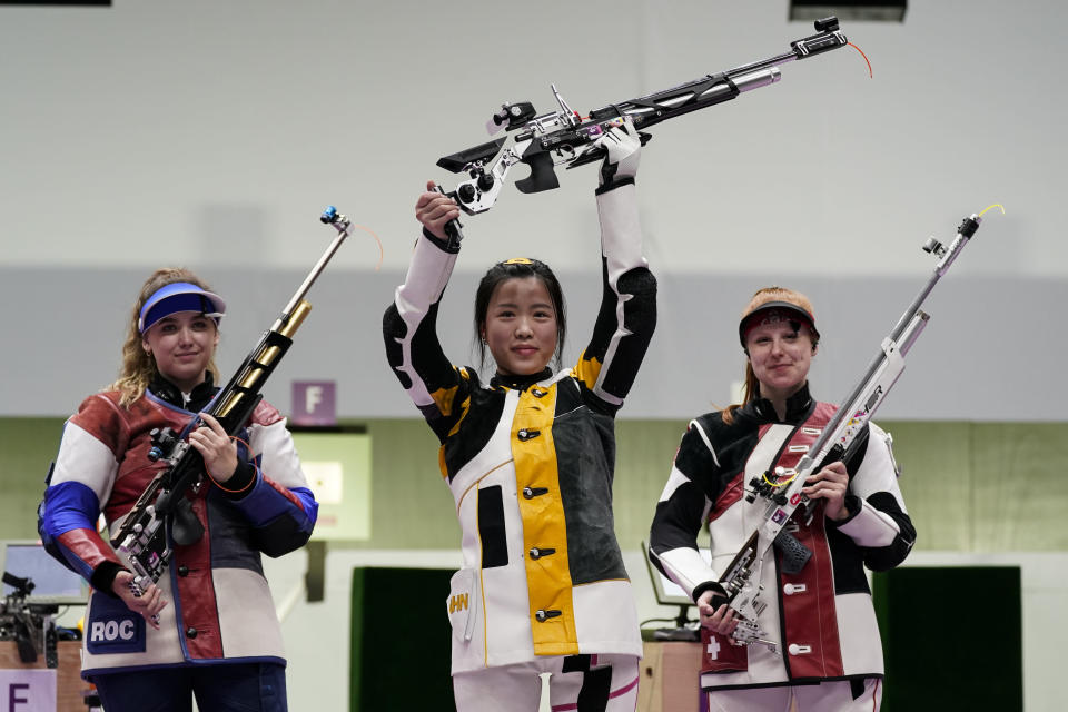 Yang Qian, of China, holds her rifle aloft after winning a gold medal in the women's 10-meter air rifle at the Asaka Shooting Range in the 2020 Summer Olympics, Saturday, July 24, 2021, in Tokyo, Japan. Anastasiia Galashina, left, of the Russian Olympic Committee, took the silver medal and Nina Christen, of Switzerland took the bronze medal.(AP Photo/Alex Brandon)
