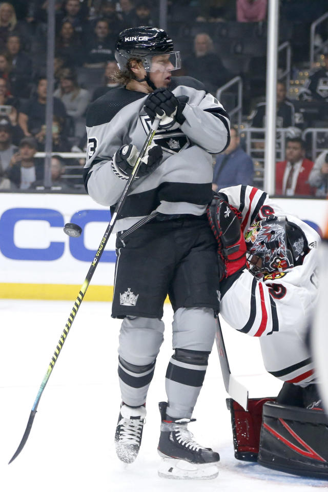 Los Angeles Kings forward Tyler Toffoli, left, gets hit by the puck as Chicago Blackhawks goalie Corey Crawford (50) defends during the second period of an NHL hockey game Saturday, Nov. 2, 2019, in Los Angeles. (AP Photo/Ringo H.W. Chiu)