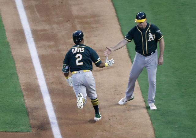 Oakland Athletics' Khris Davis (2) jogs home past third base coach Matt Williams, right, after hitting a solo home run during the second inning of the team's baseball game against the Texas Rangers in Arlington, Texas, Friday, Sept. 13, 2019. (AP Photo/Tony Gutierrez)