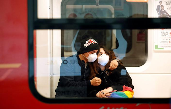 A couple wearing face masks is seen in the subway in Duomo underground station in Milan, as the country is hit by the coronavirus outbreak, Italy February 25, 2020.