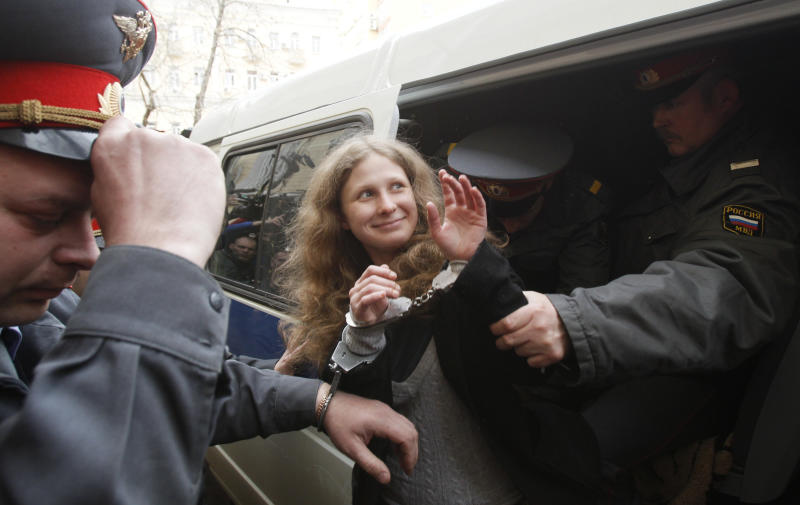 """Maria Alyokhina of Pussy Riot is escorted to a courtroom in Moscow, Russia, Thursday, April 19, 2012. Five members of the band Pussy Riot briefly seized the pulpit of Moscow's Christ the Savior Cathedral in February to chant """"Mother Mary, drive Putin away."""" Moscow court is set to consider extending the detention of three female punk rockers arrested after a surprise protest performance inside the country's main Orthodox cathedral. (AP Photo/Ivan Sekretarev)"""